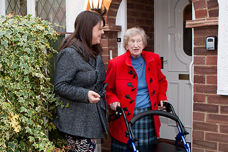 Elderly lady with walking frame alongside young smiling woman both outside a front door representing Simplyhealth's charitable giving including, charitable donations, raising money and volunteering