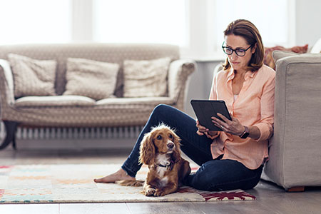 Woman with glassses in light orange casual shirt and jeans, sitting on floor in front of sofa, browsing on iPad depicting the ease of accessing a health plan wherever you are.