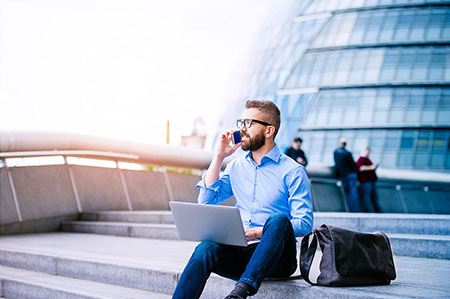 Professional man wearing shirt and glasses, sat outside a glass building on concrete steps, with a laptop on his lap and talking on the phone - showing how Simplyhealth's corporate Denplan plans can support employees in any location