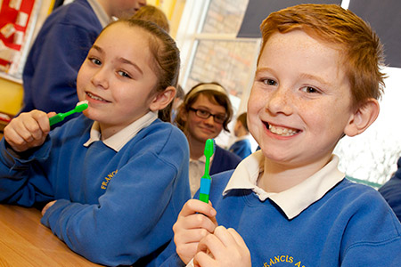 Smiling school children wearing uniform in a classroom setting holding tooth brushes to illustrate Simplyhealth's support of the Teeth Team initiative