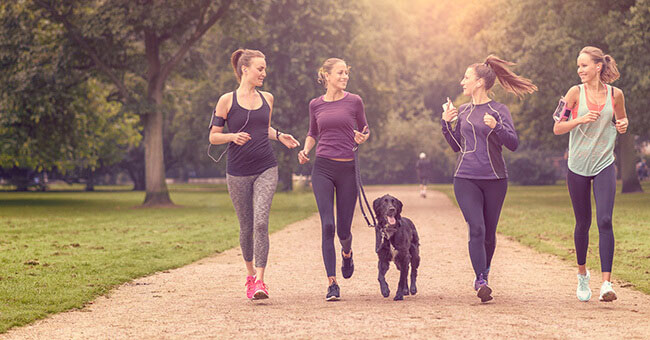 Four young women in active clothing running through a public park with pet dog