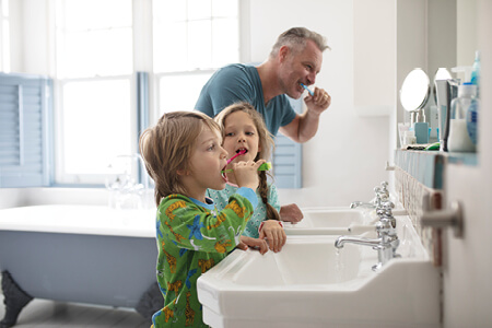 Father with young son and daughter all brushing their teeth wearing their pyjamas in the bathroom representing Simplyhealth's commitment to improving the UK's everyday health
