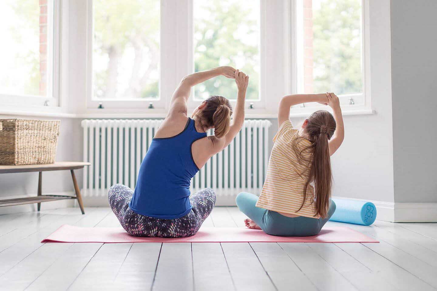 Two women practising yoga and stretching in front of a bay window, representing the importance and benefits of preventative healh plans provided by Simplyhealth.
