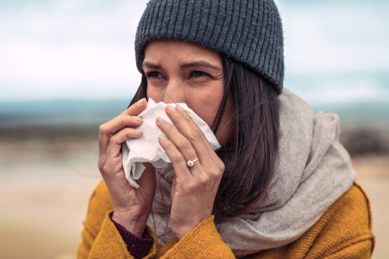 Young woman in warm clothing blowing her nose in to a tissue on beach representing how Simplyhealth helps reduce staff absence