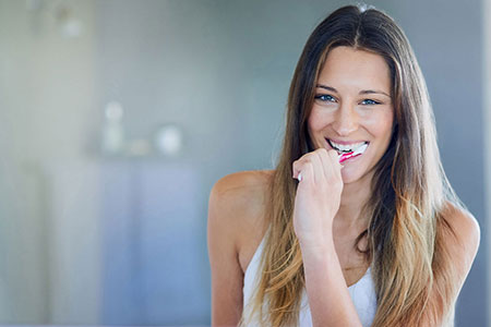 Young woman smiling at camera whilst brushing teeth with manual toothbrush showing the emotional benefits of a Simplyhealth corporate dental product