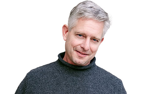 Middle aged man in turtle neck jumper, smiling at camera, represents entry to the dentists' area on website.