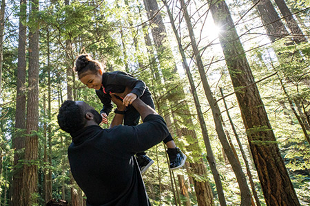 Father holding son in the air and smiling in the woods