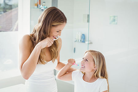Smiling mother and young daughter both dressed in white in a bathroom setting, brushing their teeth, representing how Simplyhealth's corporate dental products benefit employees' whole family