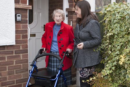 Elderly lady helped by carer