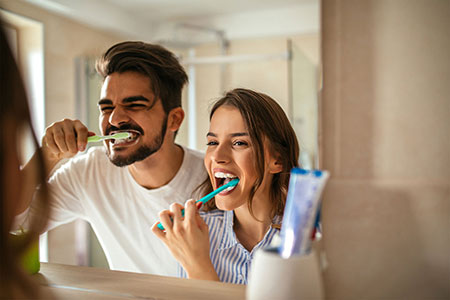 Young male and female couple grinning into mirror as they both brush their teeth with a menual toothbrush, showing how Simplyhealth corporate dental products support an employee's entire family