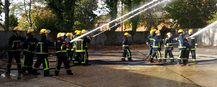 Firefighters holding a fire hose